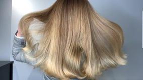 挥动她美丽,健康头发的白肤金发的妇女在治疗以后在发廊 影视素材
