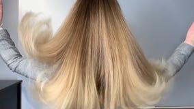 挥动她美丽,健康头发的白肤金发的妇女在治疗以后在发廊 股票视频