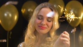 挥动孟加拉光的微笑的白肤金发的妇女在落的五彩纸屑,新年聚会下 影视素材
