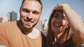 挥动对在网上录影闲谈的照相机的愉快的微笑的年轻新婚佳偶与朋友在纽约曼哈顿地平线视图  股票录像
