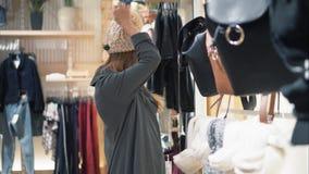 挥动年轻时髦的行家的妇女尝试在盖帽在商店和 影视素材