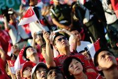 挥动新加坡标志的听众在NDP期间 库存照片