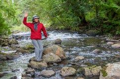 挥动由河的微笑的妇女 免版税库存照片