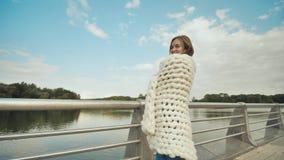 挥动美利奴绵羊的羊毛的白色格子花呢披肩快乐的女孩在公园在早期的秋天 股票录像