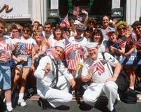 挥动美国国旗的水手和人群 免版税库存照片