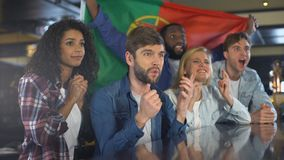 挥动葡萄牙旗子,在酒吧的观看的体育,关于丢失的比赛的翻倒的爱好者 股票视频