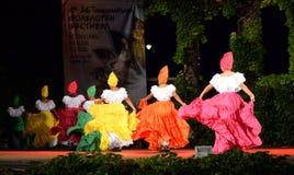 挥动裙子跳舞的哥伦比亚的民间传说舞蹈家在夜露天舞台 库存照片