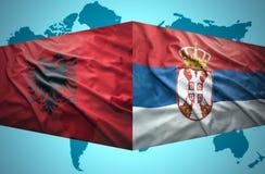 挥动阿尔巴尼亚和塞尔维亚旗子 免版税库存图片