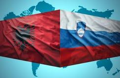 挥动阿尔巴尼亚和斯洛文尼亚旗子 免版税库存图片