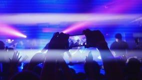 挥动他们手记录录影和拍的爱好者与巧妙的电话的照片在音乐音乐会 集会在的人人群 库存照片