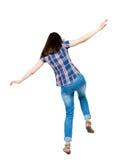 挥动他的胳膊的后面看法妇女平衡 常设女孩 免版税图库摄影