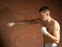 挥拳的训练的年轻拳击手 免版税库存图片