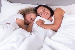紧挨着睡觉在床上的两名可爱的妇女 免版税库存照片
