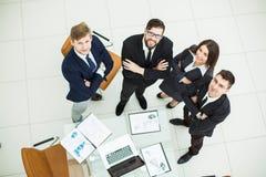 紧挨着站立在工作场所附近的成功的企业队在办公室 库存图片