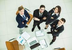 紧挨着站立在工作场所附近的成功的企业队在办公室 免版税图库摄影