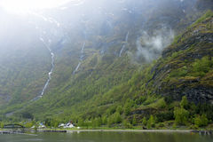 挪威村庄在有瀑布的海湾在背景中 库存照片