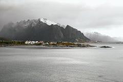 挪威海岸和一个村庄的全景在积雪覆盖的山脉前面在冬天期间在罗弗敦群岛海岛上没有的 免版税库存照片