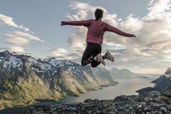挪威海湾和山与女孩跳跃 免版税库存图片