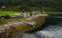 挪威海湾海岸的船库  免版税库存照片