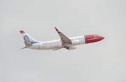 挪威语离开从特内里费岛南机场的波音737在一多云天 图库摄影