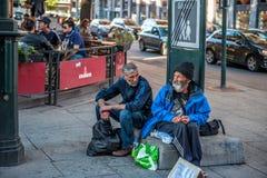 挪威,奥斯陆2013年8月01日 两个年长人请求施舍,坐在咖啡馆前面的街道 概念  库存图片