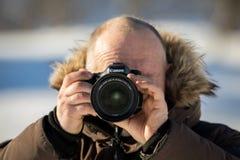 挪威, 2018年2月3日:冬天衣物的一位男性摄影师拿着与佳能24-70mm的佳能照相机2,8升 免版税图库摄影