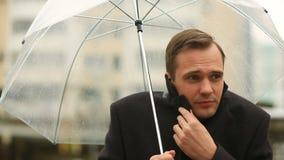 挫败由天气,站立在伞下在雨期间 衣服的不快乐的人 影视素材