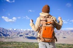 振作起来在雪山峰顶部的愉快的亚裔旅客在背景中在Leh,拉达克,印度 免版税库存照片
