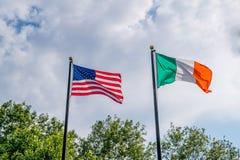 振翼反对天空蔚蓝的美国和Irland旗子,在罗德岛爱尔兰饥荒纪念品附近,上帝,美国 库存照片