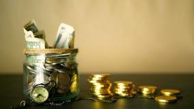 挽救在瓶子的金钱硬币 投资的标志,保留金钱概念 收集在玻璃锡的现金钞票作为moneybox 股票录像