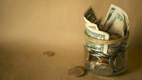 挽救在瓶子的金钱硬币 投资的标志,保留金钱概念 收集在玻璃锡的现金钞票作为moneybox 股票视频