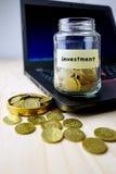 挽救概念 有金黄硬币的在桌上的玻璃瓶和膝上型计算机 免版税库存图片
