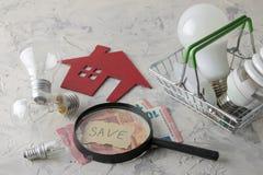 挽救电的概念 金钱、装饰房子和不同的电灯泡在一个篮子在轻的背景 库存图片