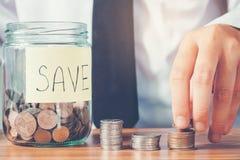 挽救金钱概念人手投入行的和硬币写财务 免版税图库摄影