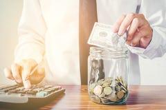 挽救金钱概念人手投入行的和硬币写财务 免版税库存图片