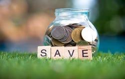 挽救金钱概念的词在与木立方体的纵横填字谜收集了 充分铸造玻璃贪心,精选的焦点 免版税图库摄影