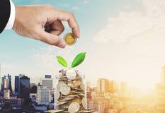 挽救金钱概念,把硬币放的商人手在玻璃瓶子容器,当植物芽发光,在日出的曼谷市上 免版税库存图片