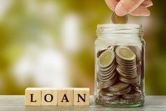 挽救,投资,贷款概念 在堆的一枚人手藏品硬币在玻璃瓶子的硬币在与木刻的木桌上和 免版税库存照片