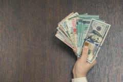 捆绑东南亚货币和一百张美元票据在女性手上 开户和旅行概念 库存照片