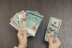 捆绑东南亚货币在女性手上和在另一个的一百张美元票据 开户和旅行概念 免版税图库摄影