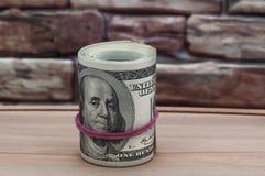 捆绑在一百美国美元票据的二千美元在一张木桌上的在砖墙的背景 库存图片