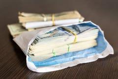 捆绑在白色信封的美国美元钞票在木桌上 次要非法经济概念 信封薪水 的贿赂 免版税库存图片