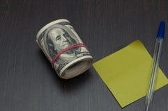 捆绑美国美元在一张木桌、板料笔记的和笔上的票据 免版税库存照片
