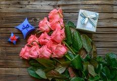 捆绑玫瑰和礼物在桌上 库存图片