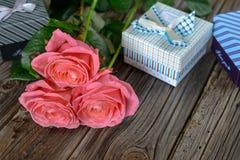 捆绑玫瑰和礼物在桌上 库存照片
