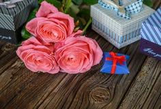 捆绑玫瑰和礼物在桌上 免版税库存照片
