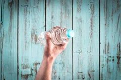 捉住一个瓶水的手 免版税库存图片