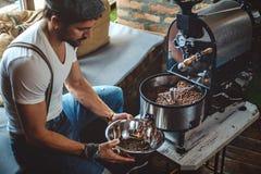 捉住从烘烤器的行家烤咖啡与盘 库存照片