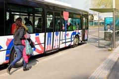 捉住公共汽车的妇女赛跑在汽车站 免版税库存照片