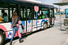 捉住公共汽车的妇女赛跑 图库摄影